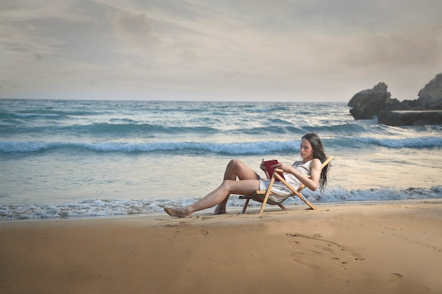 Relaxing and reading on the beach Premium Photo
