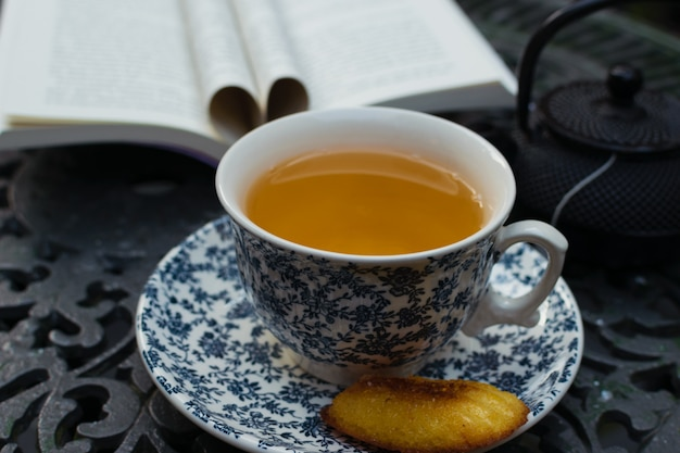 Relaxing tea time and reading at the porch on an iron table. world day book Premium Photo