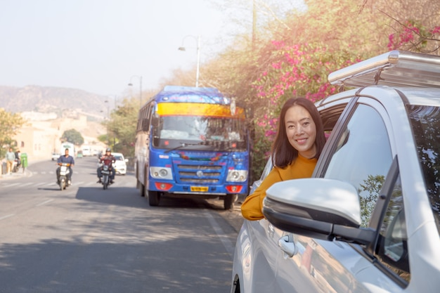 Relaxing woman on summer roadtrip leaning out car window travel vacation concept. Premium Photo