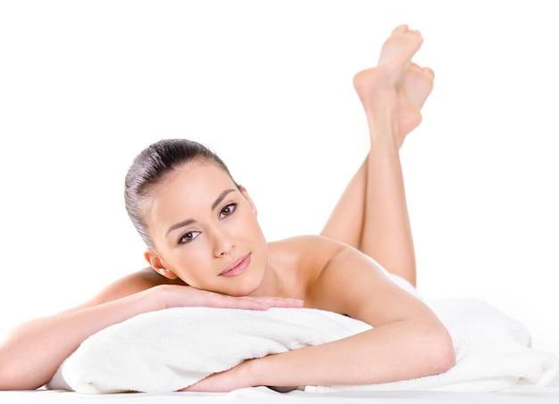 Расслабляющая молодая красивая женщина со свежей кожей - белый фон. лежа на кровати Бесплатные Фотографии