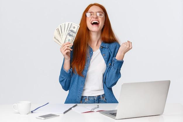 Облегченная и счастливая девушка становится богатой после того, как она много делает, пожимает руки, нажимает на кулак да и поднимает голову в небо в восторге, держит большие деньги, деньги рядом с дест с ноутбуком, белая стена Premium Фотографии