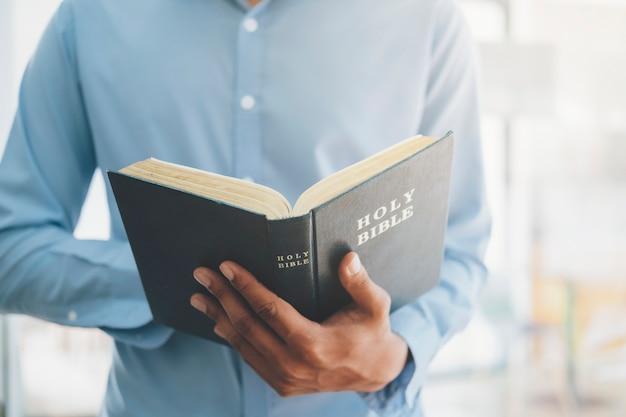 宗教キリスト教の概念。神聖なキリスト教の聖書を保持し、読んでいる男。 Premium写真