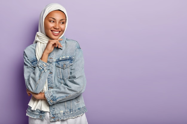 Religious arabic woman has cheerful expression, covers head with white hijab, wears denim jacket, holds chin, looks away, stands against purple wall. people, ethnicity and faith concept Free Photo