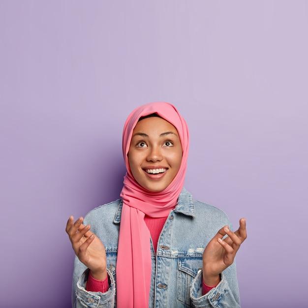 Религиозная жизнерадостная женщина имеет исламские взгляды, поднимает ладони, молится и с надеждой смотрит вверх Бесплатные Фотографии