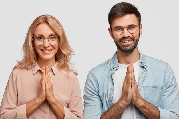 幸せな表情で宗教的な家族のカップル、祈りのジェスチャーをし、幸福を信じる 無料写真