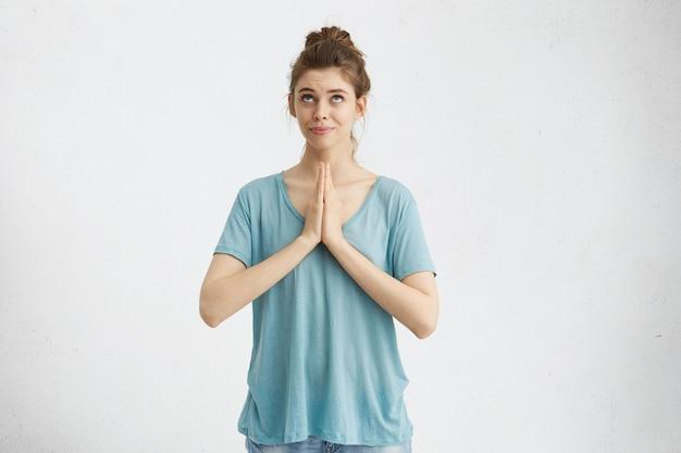 Религиозная девушка с волосами, собранными в узел, сжимает ладони вместе и смотрит вверх, молясь богу, умоляя о прощении или прося осуществить свою мечту. человеческие эмоции и чувства Бесплатные Фотографии