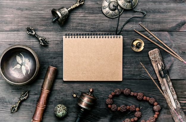 Religious musical instruments for meditation and alternative medicine, blank notebook with brown sheets Premium Photo