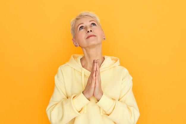 希望に満ちた目でポーズをとる宗教的な不幸な女性年金受給者は、祈り、懇願し、神に助けと導きを求め、困難な時期に落ち込んでいる間、手をつないで押し上げました 無料写真