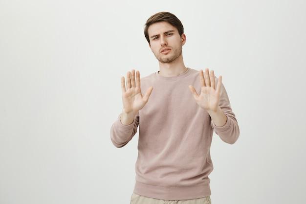 Неохотно недовольный мужчина пожимает руку в жесте отказа Бесплатные Фотографии