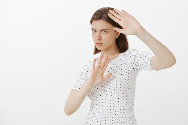 Donna seria riluttante che sta lontano da qualcosa, alzando le mani in gesto di arresto, difendendosi Foto Gratuite