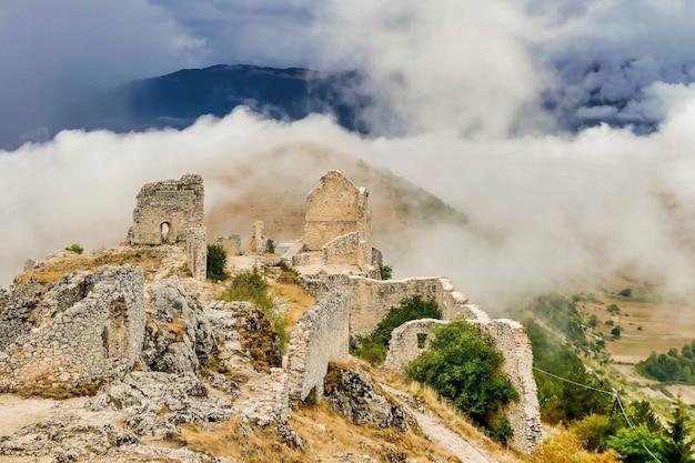 Resti di un edificio avvolto dalla nebbia scesa dalle montagne Foto Gratuite