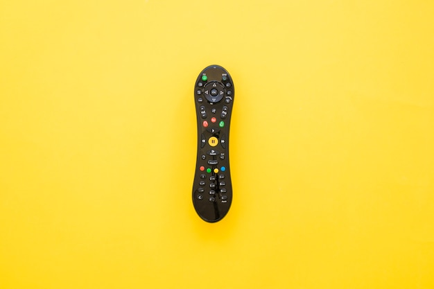 Remote control on yellow background Free Photo