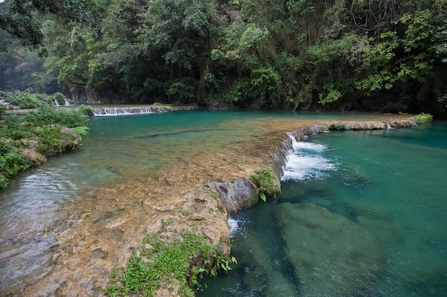 Semuc champeyのジャングルの滝。緑豊かな熱帯雨林の新鮮な青緑色の水。 Premium写真