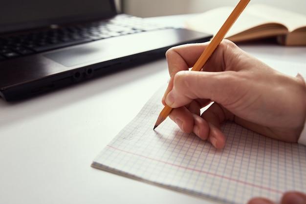 원격 작업. 여자는 노트북에 노트를 만들고 연구를 위해 노트북을 사용합니다. 원격 교육 및 E- 러닝 개념 프리미엄 사진