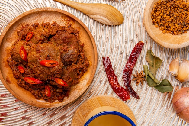 Rendang pork or rendang babi rendang babi is often described as a rich dish of meat that has been slow cooked and braised in a coconut milk seasoned with a herb and spice mixture Premium Photo