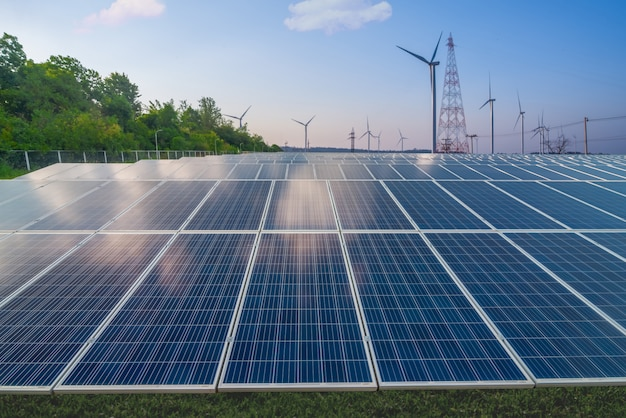 Renewable energy, solar panels and wind turbines on green grass in blue sky Premium Photo