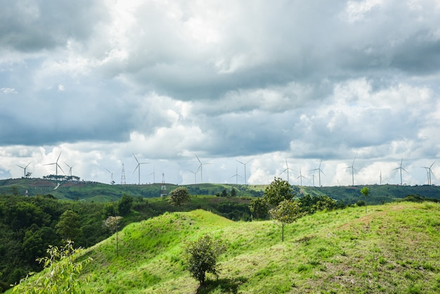Renewable energy windmill wind turbine on mountain landscape with high voltage pole and electric pole on hills / Premium Photo