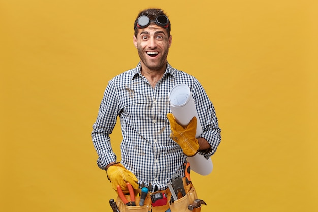 Renovation and occupation concept. young handyman wearing protective goggles, shirt and kit full of tools holding blueprint looking with excited expression going to have rest after work Free Photo