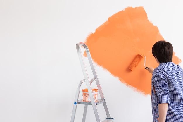 リフォーム、改装、修理のコンセプト-新しい家の中年女性の絵画の壁。 Premium写真