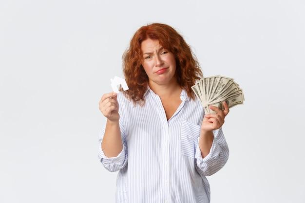 Аренда, покупка недвижимости и концепции недвижимости. неуравновешенная и грустная рыжая женщина средних лет с деньгами и карточкой на дом, у нее недостаточно денег, нужна ссуда для покупки, белая стена. Бесплатные Фотографии