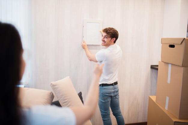 수리, 숙박 및 부동산 개념. 새 집으로 이사하고 벽에 그림이나 사진 프레임을 걸고 웃는 커플 프리미엄 사진