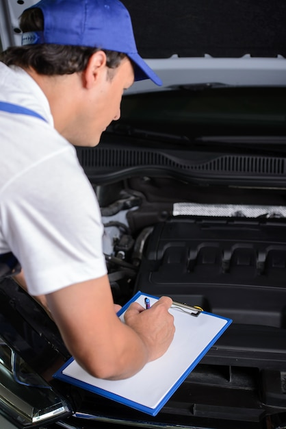 Repair shop man is standing next to car with open hood. Premium Photo