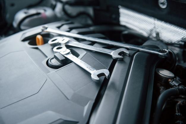 Strumenti di riparazione sdraiati sul motore dell'automobile sotto il cofano Foto Gratuite