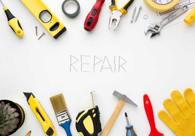 Repair word written with nails surrounded by repair kit Free Photo