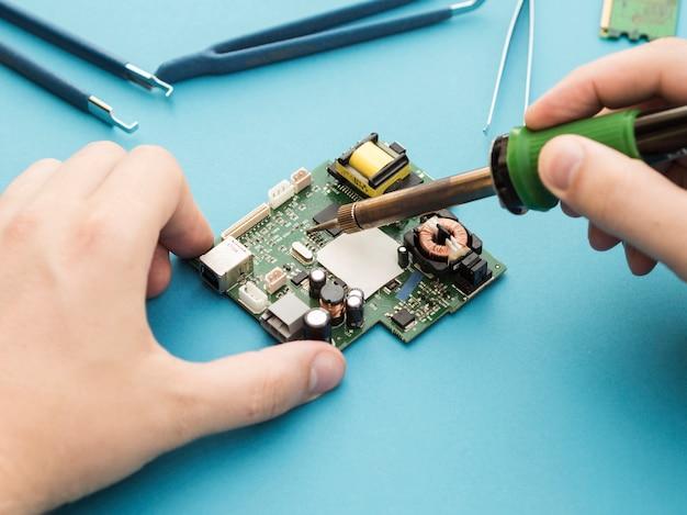 Repairing a circuit using soldering iron Free Photo