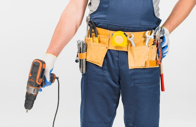 Repairman in blue overall holding drill Free Photo