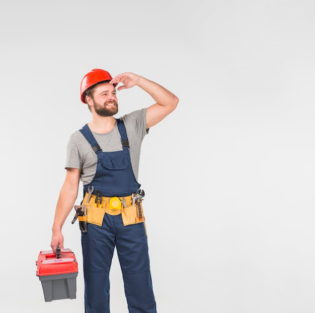 Repairman in blue overall with tool box looking away Free Photo