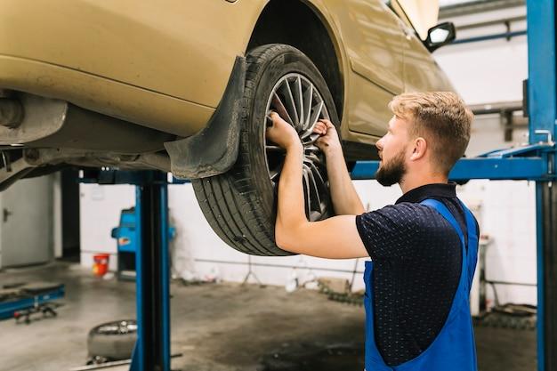 Repairman fixing tyre in shop Free Photo