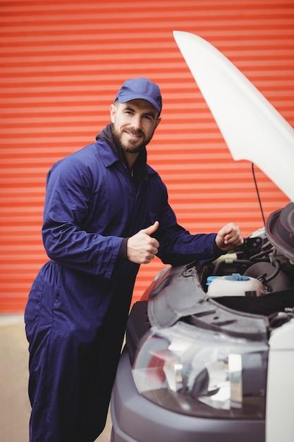 Repairman fixing  a van with thumbs up Premium Photo