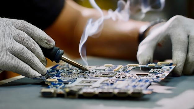 Repairman in gloves is soldering motherboard of computer device in workshop Premium Photo