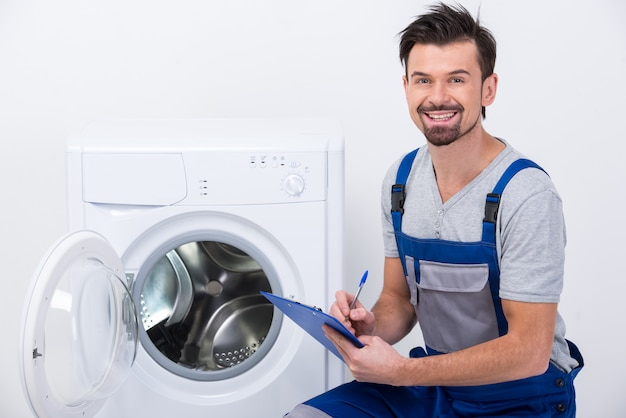 Repairman is repairing a washing machine. Premium Photo