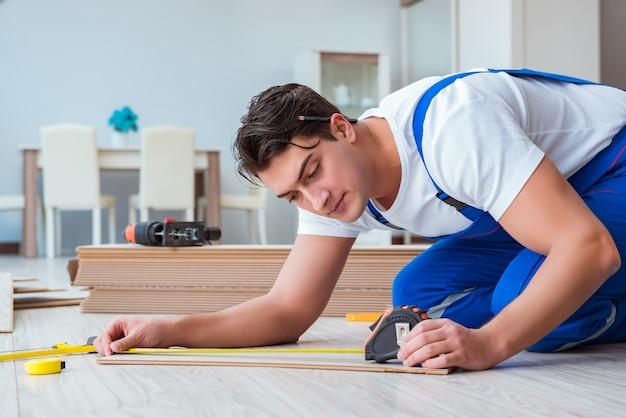 Repairman laying laminate flooring at home Premium Photo