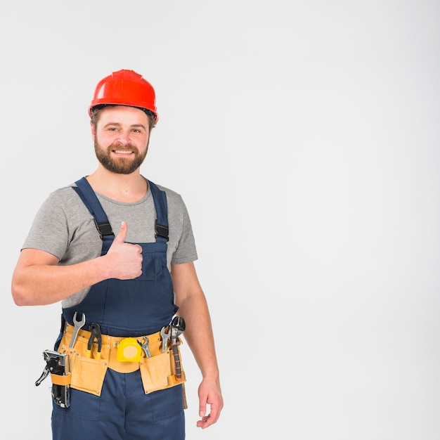 Repairman in overall and helmet showing thumb up Free Photo