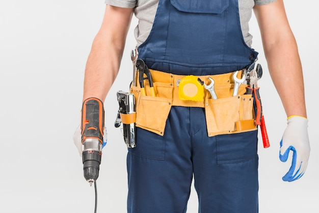 Repairman in overall holding drill Free Photo
