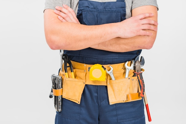 Repairman in overall standing with crossed arms Premium Photo