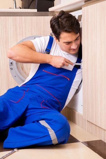 Repairman repairing washing machine at kitchen Premium Photo