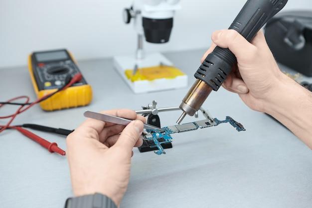핀셋과 다리미를 사용하여 손상된 스마트 폰을 수리하면서 마더 보드의 부품을 납땜하는 수리공 무료 사진