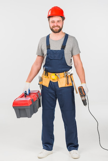 Repairman standing with tool box and drill Free Photo