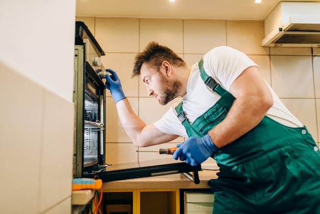 Repairman in uniform checks the oven, technician. professional worker makes repairs around the house, home repairing service Premium Photo