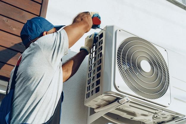 Repairman in uniform installing the outside unit of air conditioner Premium Photo
