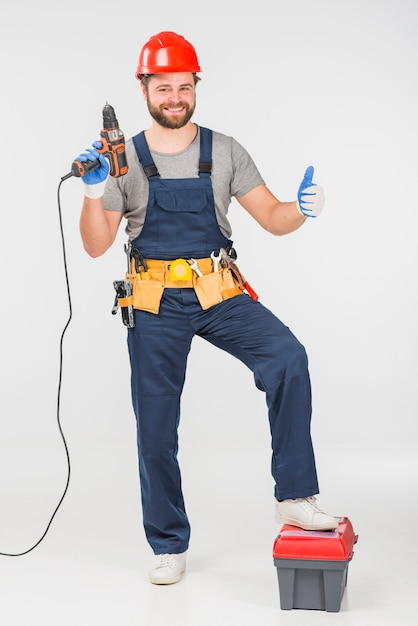 Repairman with drill showing thumb up Free Photo