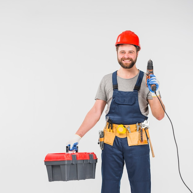 Repairman with tool box holding drill Free Photo