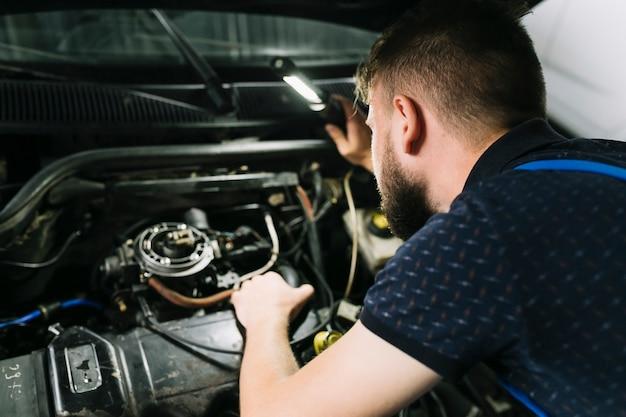 Repairmen inspecting vehicle engine Free Photo