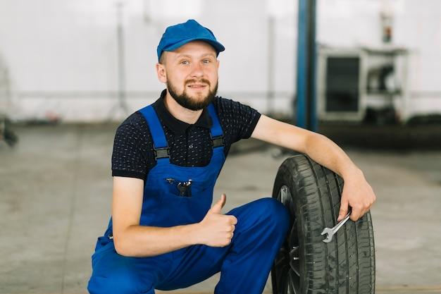 Repairmen and tire at garage Free Photo
