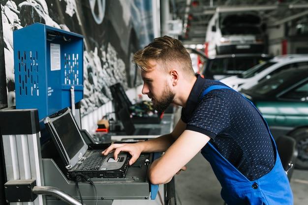 Repairmen using laptop at workshop Premium Photo