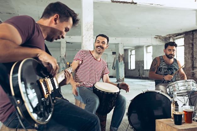 ロックミュージックバンドの繰り返し。ロフトでのベースギタープレーヤー、エレキギタープレーヤー、ドラマー。 無料写真